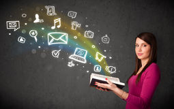 Jeune femme lisant un livre avec des icônes de multimédia sortant de t Photographie stock libre de droits