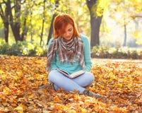 Jeune femme lisant un livre en nature Image libre de droits