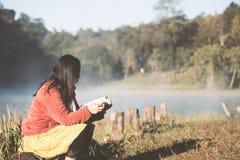 Jeune femme lisant un livre en parc naturel avec la fraîcheur photographie stock