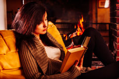 Jeune femme lisant un livre par la cheminée photos stock