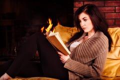 Jeune femme lisant un livre par la cheminée photos libres de droits