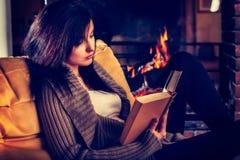 Jeune femme lisant un livre par la cheminée image libre de droits