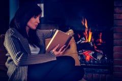 Jeune femme lisant un livre par la cheminée image stock