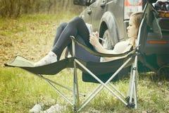 Jeune femme lisant un livre se reposant dans une chaise dehors Photo stock