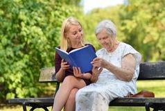 Jeune femme lisant une femme agée de livre Images stock