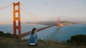 Jeune femme locale de vue arrière seul s'asseyant au paysage épique méditant à la belle vue de coucher du soleil chez golden gate clips vidéos