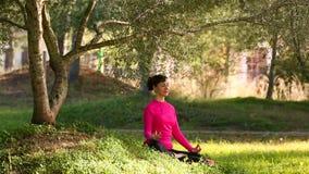 Jeune femme méditant en parc banque de vidéos