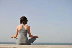 Jeune femme méditant sur la plage Photos stock