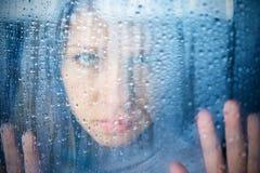 Jeune femme mélancolique et triste à l'hublot sous la pluie Photographie stock libre de droits