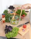 Jeune femme mélangeant la salade fraîche dans la cuisine images libres de droits