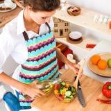 Jeune femme mélangeant la salade fraîche tenant le bureau proche Image stock