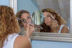 Jeune femme magnifique appliquant le maquillage d'oeil photo stock