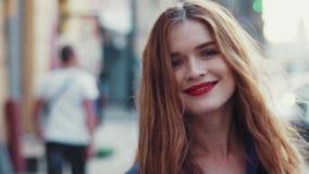 Jeune femme magnifique avec de beaux yeux bleus et longs cheveux d'or, avec un rouge à lèvres rouge lumineux La jeune dame attira banque de vidéos