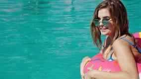 Jeune femme magnifique avec des lunettes de soleil dans le bikini noir se situant dans le flotteur rose gonflable de beignet dans banque de vidéos