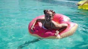 Jeune femme magnifique avec des lunettes de soleil dans le bikini noir se situant dans le flotteur rose gonflable de beignet dans clips vidéos