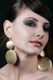 Jeune femme magnifique avec le maquillage et les grandes boucles d'oreille Photos stock