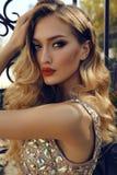 Jeune femme magnifique avec les cheveux bouclés blonds dans la robe luxueuse images libres de droits
