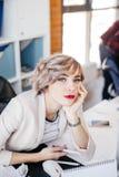 Jeune femme magnifique avec les cheveux courts justes se penchant avec la main sur son menton images stock