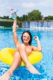 Jeune femme magnifique avec les lunettes de soleil et le pot avec la boisson froide se reposant dans le flotteur gonflable dans l image stock