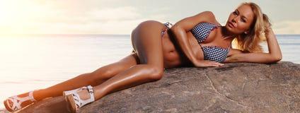 Jeune femme magnifique détendant sur la plage photographie stock