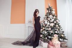 Jeune femme magnifique dans la robe noire avec le maquillage parfait et les cheveux image stock