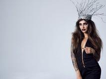 Jeune femme magnifique dans une image de sorcière en bois sexy image stock