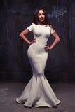 Jeune femme magnifique dans une maxi robe en queue de poisson blanche au-dessus de blac Photo stock