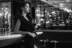 Jeune femme magnifique de brune dans la robe foncée avec du vin photographie stock