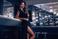 Jeune femme magnifique de brune dans la robe foncée avec du vin image stock