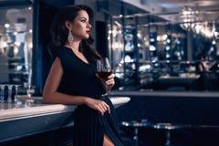 Jeune femme magnifique de brune dans la robe foncée avec du vin images stock