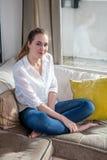 Jeune femme magnifique de sourire s'asseyant pour le bonheur et le bien-être photo stock