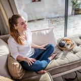 Jeune femme magnifique de sourire s'asseyant sur le sofa confortable avec le petit déjeuner photos stock
