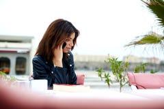 Jeune femme magnifique parlant au téléphone portable tout en se reposant en café de trottoir Images stock