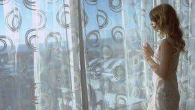 Jeune femme magnifique posant tout en se tenant à la fenêtre dans une chambre d'hôtel banque de vidéos