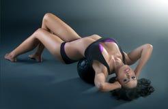 Jeune femme magnifique s'étendant sur la boule d'ajustement, faisant la séance d'entraînement photos libres de droits