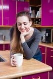 Jeune femme magnifique souriant avec du son café au-dessus d'un fond de cuisine Photos stock