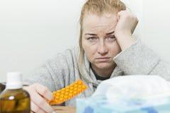 Jeune femme malade avec le mal de tête énorme Photos stock