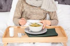 Jeune femme malade mangeant du bouillon pour traiter le froid photos libres de droits