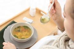 Jeune femme malade mangeant du bouillon pour traiter le froid dans le lit photographie stock libre de droits