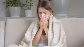 Jeune femme malade s'asseyant sur le sofa et le nez de soufflement dans le mouchoir banque de vidéos