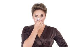 Jeune femme malade soufflant son nez photo stock