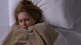 Jeune femme malade tremblant avec le froid, couvrant la couverture dans le lit, symptômes de grippe clips vidéos