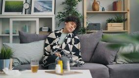 Jeune femme malheureuse avec le thermomètre vérifiant la température faisant une sieste alors sur le divan banque de vidéos