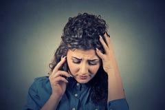 Jeune femme malheureuse parlant au téléphone portable regardant vers le bas Photo libre de droits