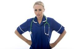 Jeune femme malheureuse sévère attirante posant en tant qu'un médecin ou infirmière photo libre de droits