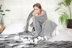 Jeune femme malheureuse s'asseyant sur le lit enveloppé dans le malade couvrant chaud de sentiment avec la grippe images libres de droits