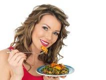 Jeune femme mangeant d'un poulet Tikka et de la salade de riz Image libre de droits