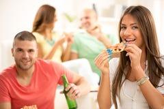 Jeune femme mangeant de la pizza Image stock
