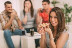 Jeune femme mangeant de la pizza Photographie stock libre de droits