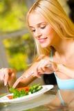 Jeune femme mangeant de la salade Photographie stock libre de droits